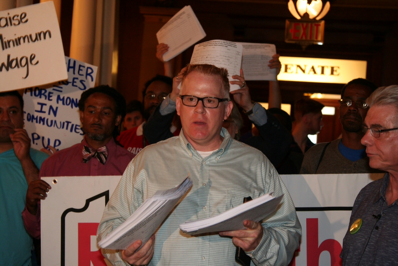 Chuck Harford, a deli worker from Perry County, holds up the petitions as he talks about trying to get by on low wages.